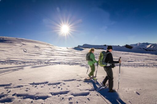 A couple holding hiking poles and walking in the snow